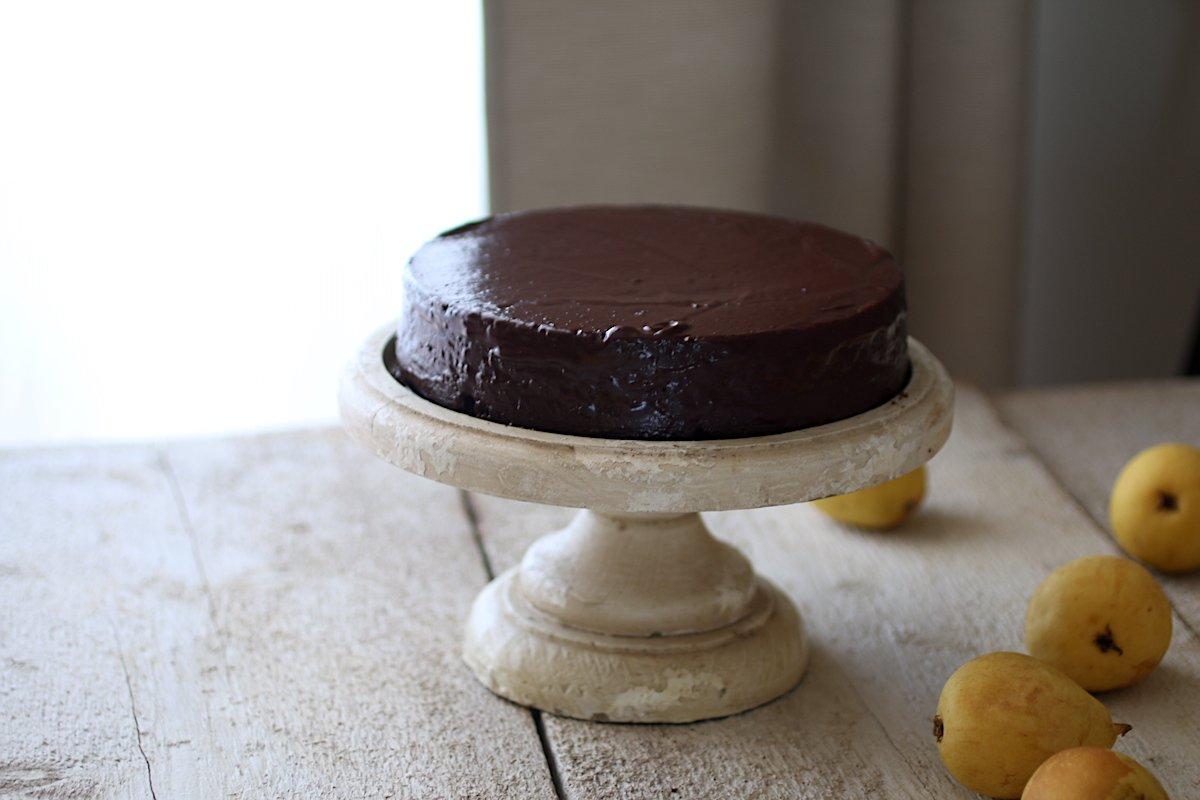 Torta al cioccolato sull'alzata di legno con le pere sul tavolo