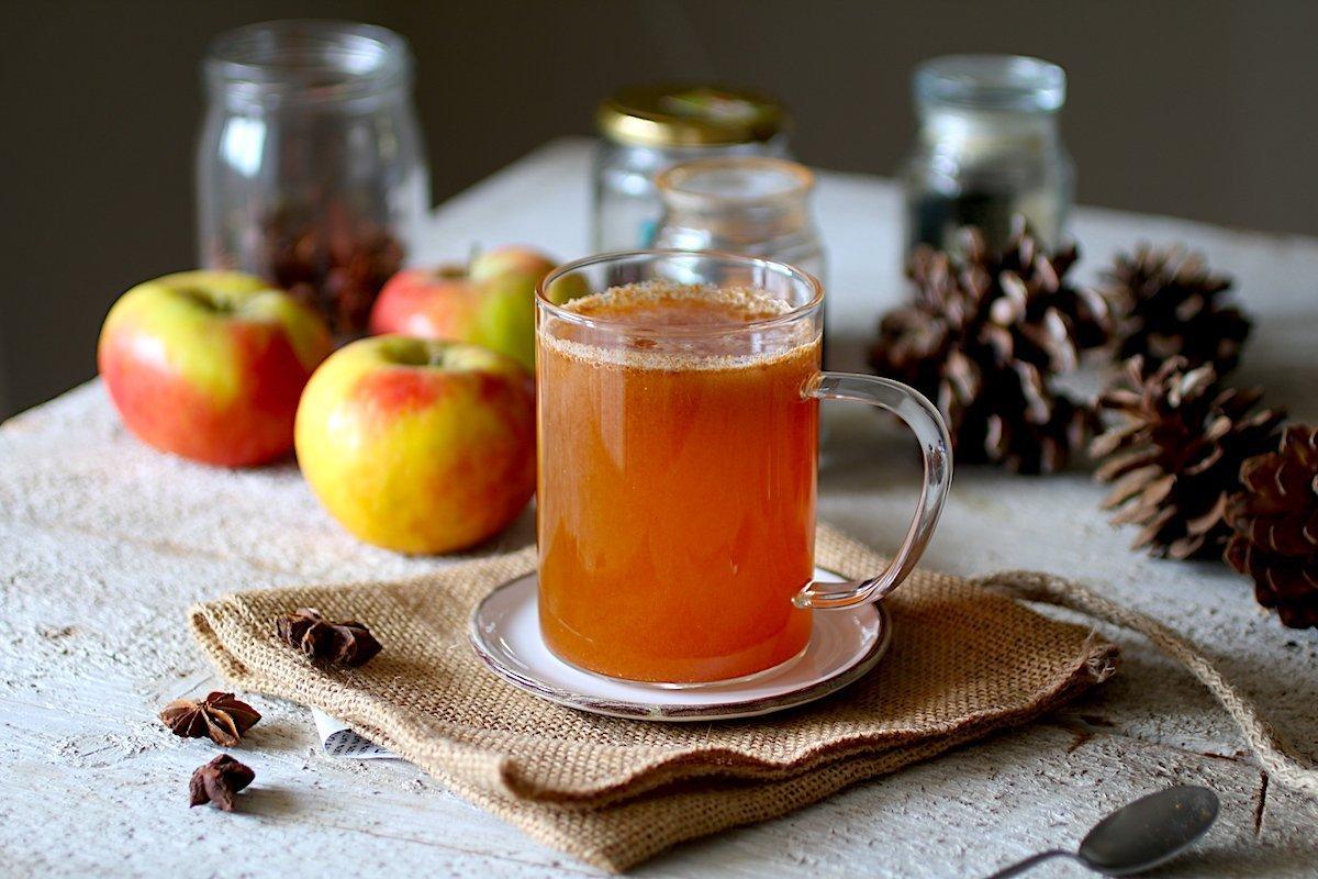 Succo di mele in una tazza trasparente al centro di un tavolo