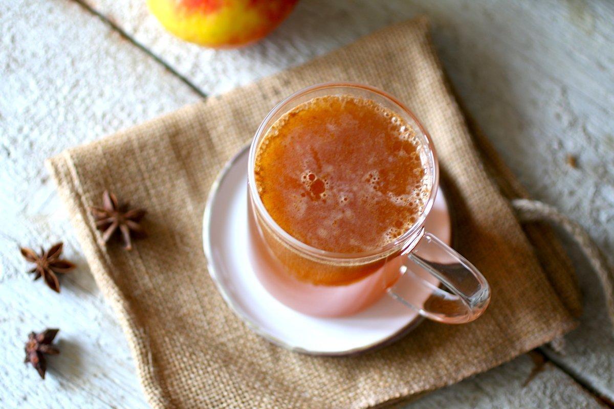 Succo di mele in una tazza vista dall'alto con anice stellato