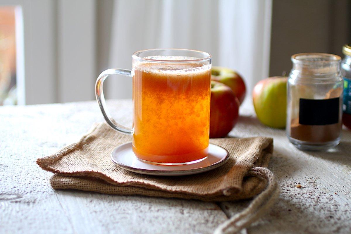 Una tazza trasparente con il succo di mele su un tavolo di legno