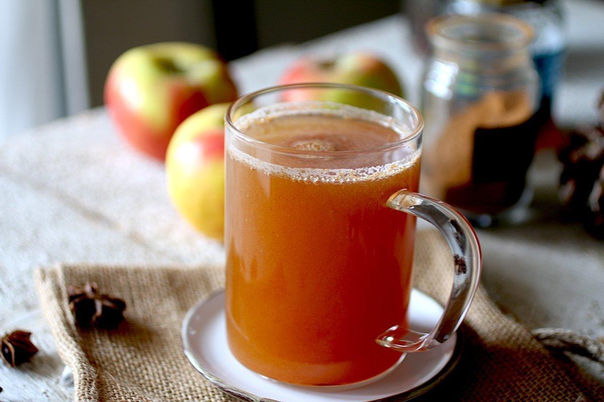 Tazza con succo di mele, anice stellato, mele e cannella sullo sfondo